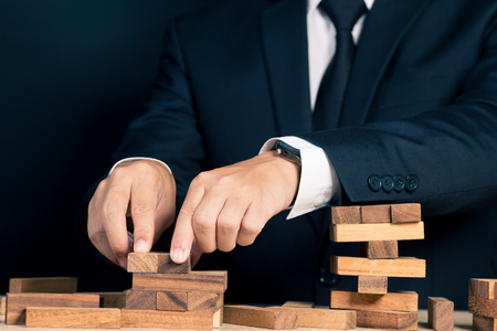fragile economy: Businessman Builds a Tower Stock Photo
