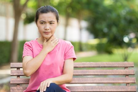 Frau hat Halsschmerzen im Garten Standard-Bild