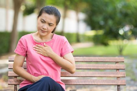 Woman has reflux acids in the garden Stock Photo