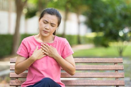 Woman has reflux acids in the garden Banque d'images