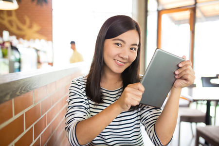 Woman typing tablet in cafe Stock Photo