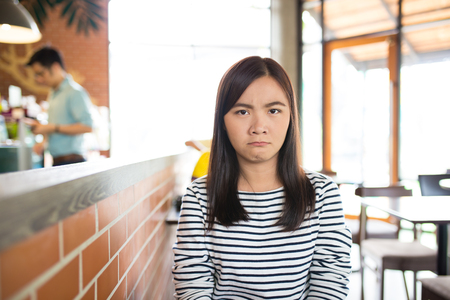 Angry woman sitting in the cafe