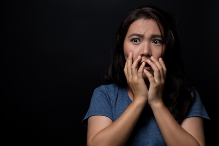 Shocked woman on isolated black background Imagens