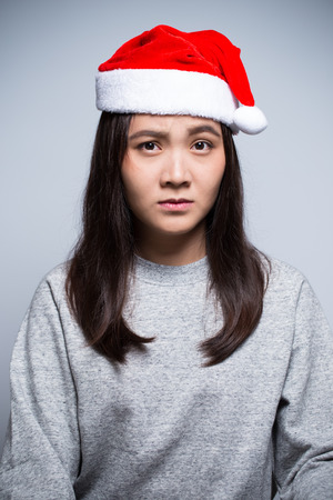 ruminate: Woman wearing a santa hat thoughtful on isolated background