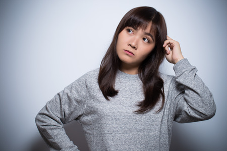 ruminate: Thoughtful woman on isolated background Stock Photo