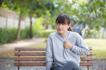 Woman has reflux acids at park Stock Photo