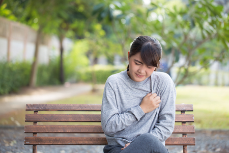Woman has chest pain at park Stock Photo