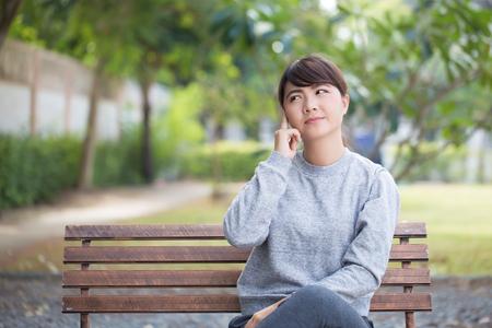 HESITATE: Woman thinking at park Stock Photo
