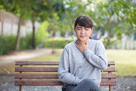 aching: Woman has sore throat at park