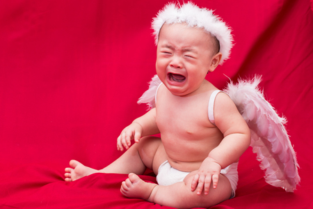 Sad baby cupid on red background