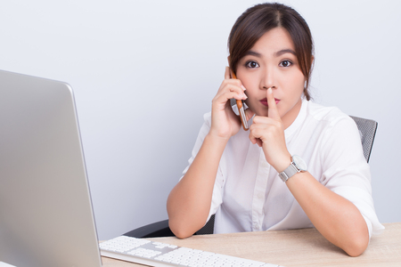 secretly: Woman calling the phone and make quiet gesture in office Stock Photo