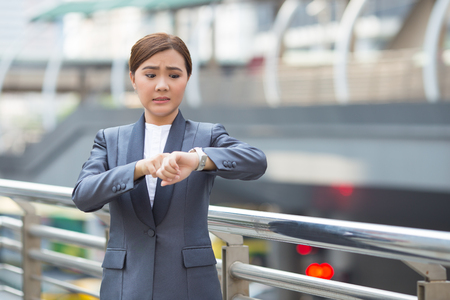 Businesswoman check her watch and she is late