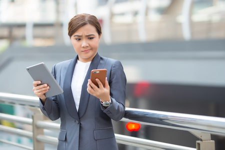 Businesswoman use tablet and smartphone has worry