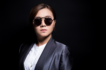 Seriously businesswoman wearing sun glasses on isolated background