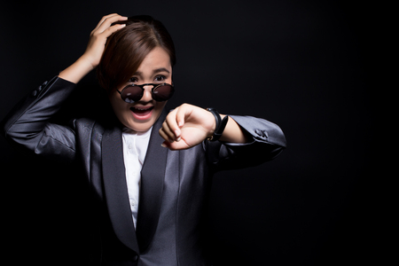 Woman wearing sun glassesin black suit check her watch she is late Stok Fotoğraf