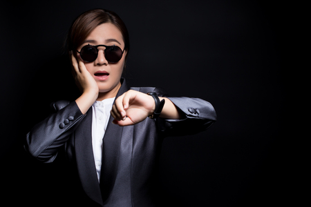 reminding: Woman wearing sun glassesin black suit check her watch she is late Stock Photo