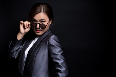 vehement: Seriously businesswoman wearing sun glasses on isolated background
