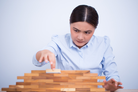 Woman be careful to build a tower puzzle Stock Photo