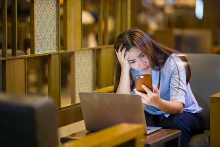 Woman calling on smartphone in night time at cafe feel upset