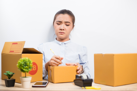 Woman writing on the box but she forgot detail