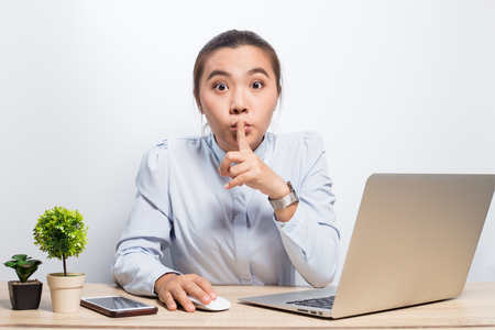 Woman make quiet gesture at office