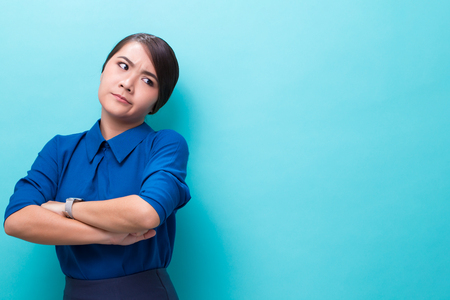 Angry woman standing on isolated blue background