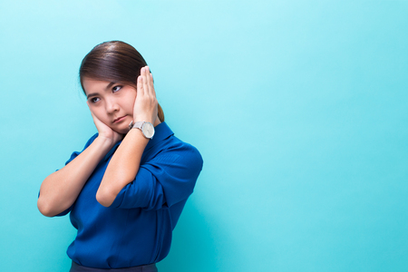 Asian woman covers ears with hands on isolated background