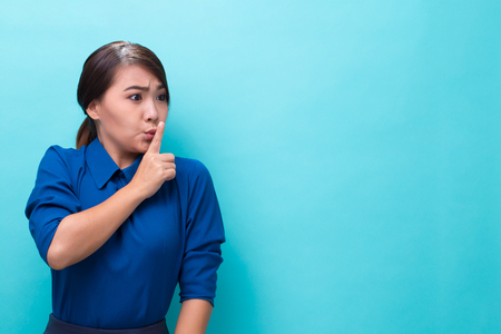 Asian woman making quiet gesture on isolated background