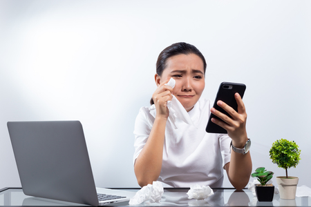 Woman look at smartphone and crying Фото со стока