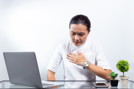 Woman has chest pain at office Foto de archivo