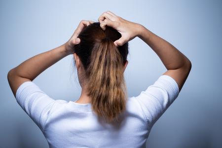 Frau kratzt sich am Kopf