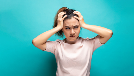 Portrait of angry woman standing on blue background  Reklamní fotografie