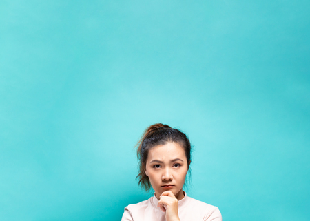 Portrait of serious woman on a blue background