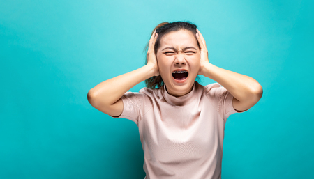 Portrait of angry woman standing on blue background Stock Photo