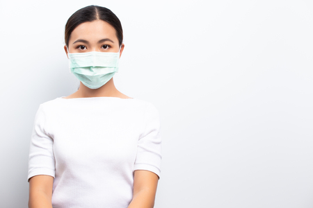 Asian women wear protective masks isolated over white