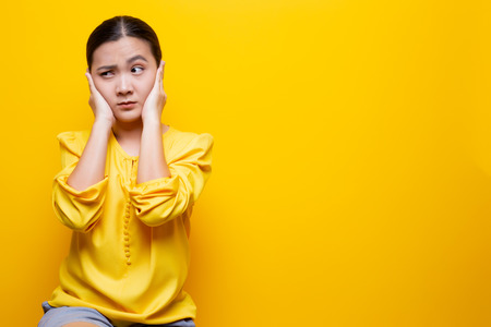 Woman covering her ears and standing isolated over yellow Stock Photo