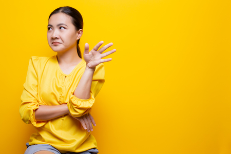 Woman show disgust gesture isolated over yellow 免版税图像