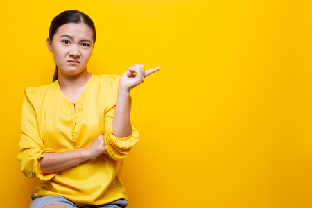 Woman show disgust gesture isolated over yellow Stock Photo