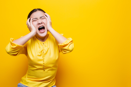 Angry woman screaming isolated over yellow Stock Photo