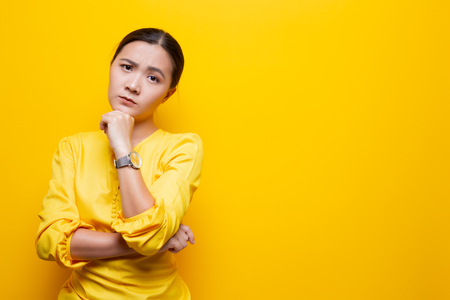 Woman feel confused isolated over yellow Stock Photo