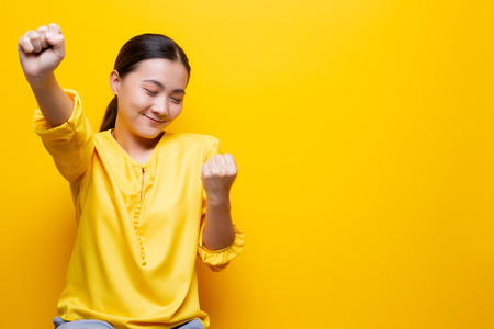 Happy woman make winning gesture isolated over yellow