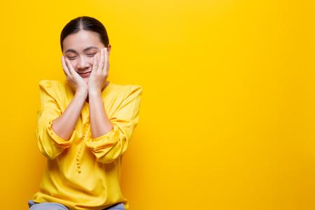 Woman feel shy standing isolated over yellow