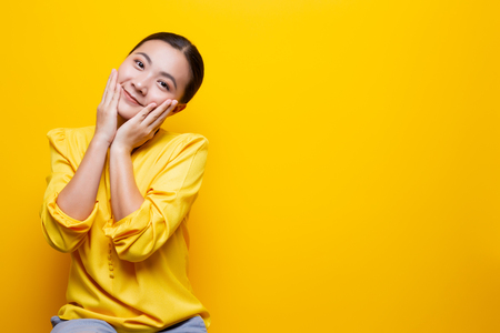 Woman feel shy standing isolated over yellow