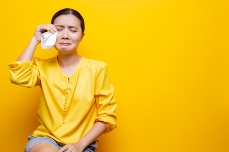 Sad woman crying and wipe her tears by tissue paper Stockfoto