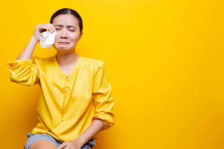 Treurige vrouw huilt en veegt haar tranen af met papieren zakdoekje Stockfoto