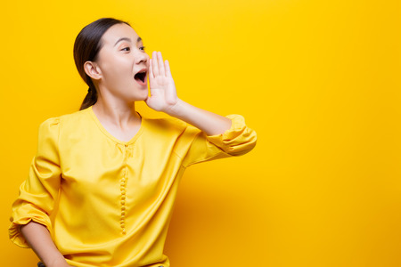 Happy woman making shout gesture isolated over yellow
