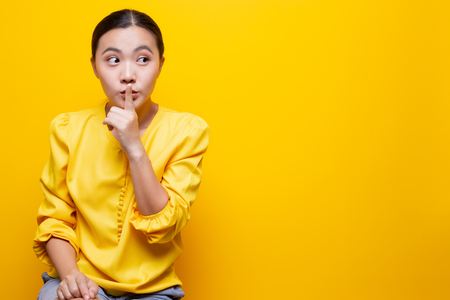 Woman show a quiet sign isolated over yellow