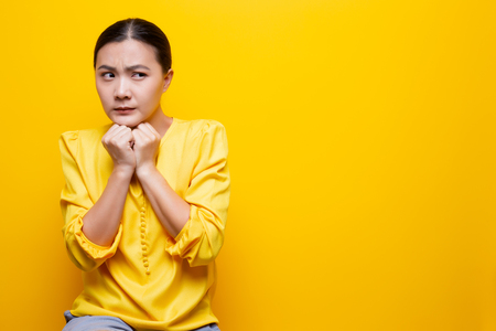 Woman feel scared standing isolated over yellow