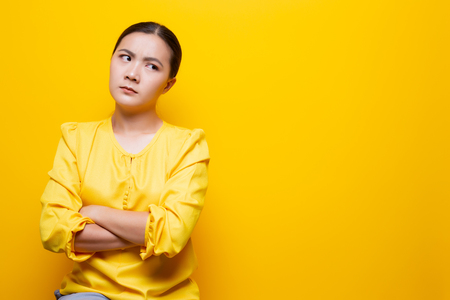 Angry woman standing isolated over yellow