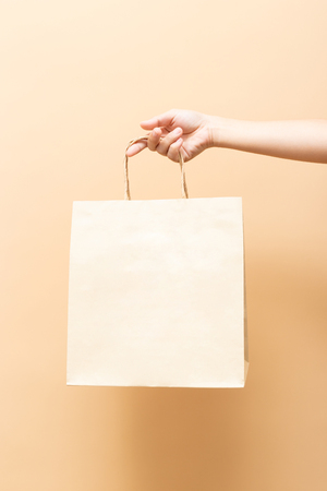 Hand holding a paper bag isolated Foto de archivo